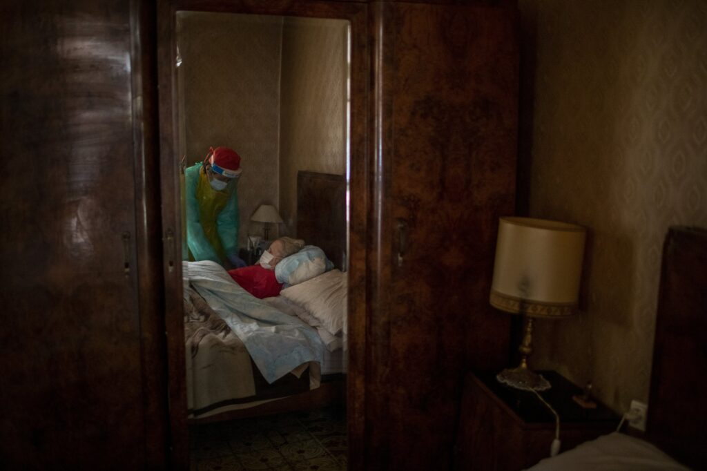 """Γυναικα που εινια κατάκοιτη με άνοια , δεχεται την φροντιδα απο νοσοκομα στην Βαρκελώνη. Ο αντρς της που έχει επιζήσει τον 2ο Παγκόσμιο πόλεμο δηλώνει:"""" Επέζησα την μεγάλη πείνα κατα τη διάρκεια του πολέμου. Εύχομαι να τα καταφέρουμε και στην πανδημία"""" . 2020 AP Emilio Morenatti"""