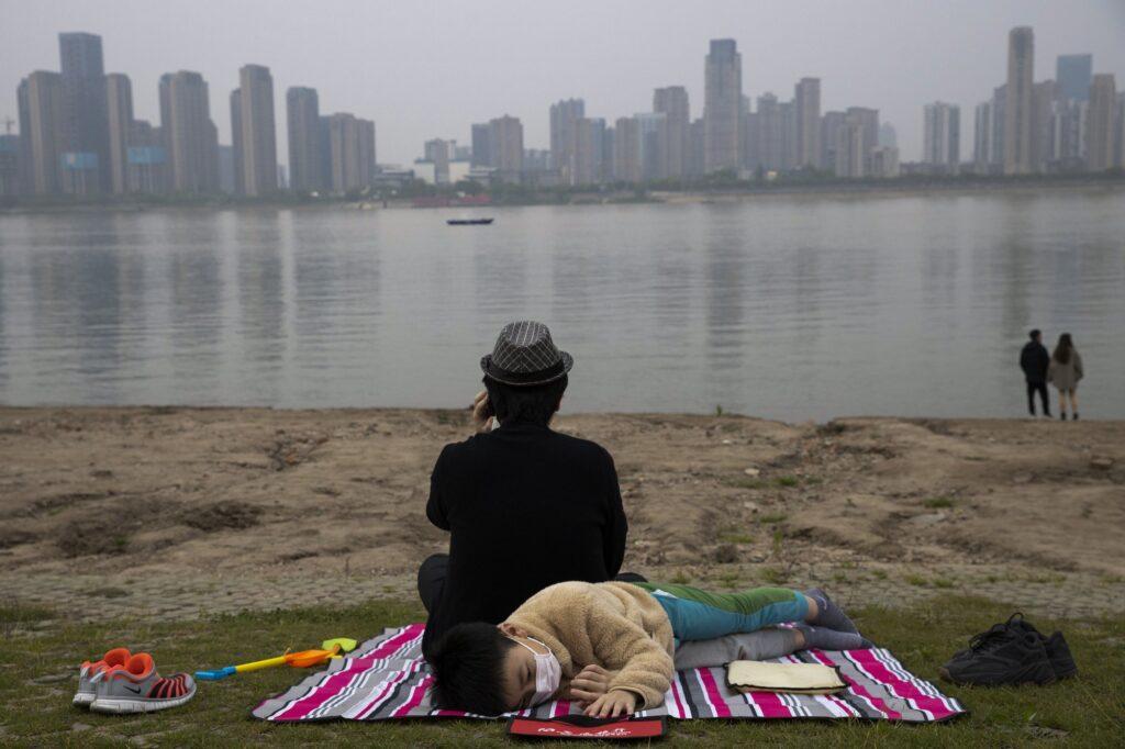 Ενα αγόρι φοράει μάσκα και κάθεται δίπλα σε ένα ποτάμι στην πόλη Wuhan. 16 Απριλίου 2020.   AP 2020 Photo/ Ng Han Guan